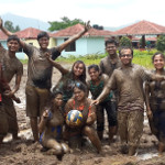group of friends playing in the mud